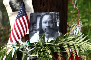 Photos of Samuel DuBose hang on a pole at a memorial, Wednesday July 29, 2015 in Cincinnati, near where he was shot and killed by a University of Cincinnati police office. Murder and manslaughter charges were announced against University of Cincinnati Police Officer Ray Tensing for the traffic stop shooting death of DuBose. (AP Photo/Tom Uhlman)